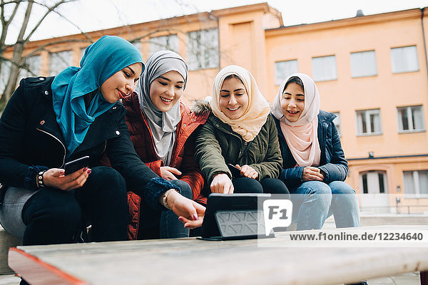 Happy female Muslim friends sitting with digital tablet on bench in city