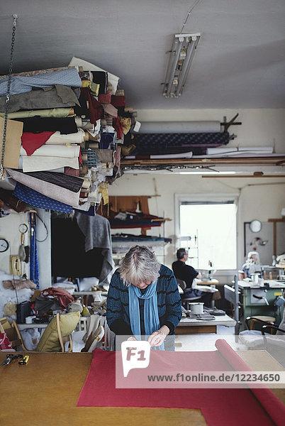 Seniorin beim Nähen von rotem Stoff im Stehen an der Werkbank in der Werkstatt