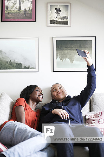 Mutter und Sohn nehmen Selfie mit dem Handy auf dem Sofa mit nach Hause.