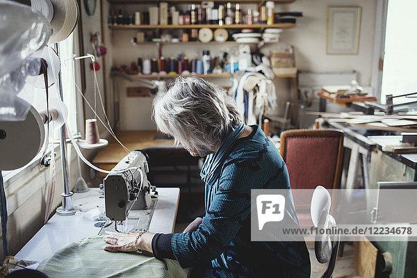 Seniorin mit Nähmaschine in der Werkstatt