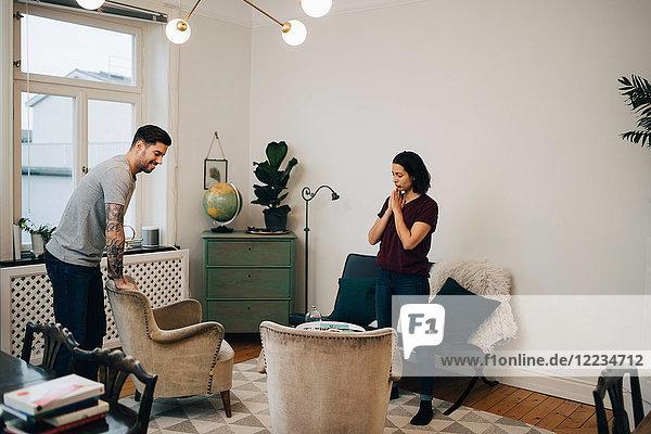 Volle Länge von Mann und Frau beim Einrichten des Sofas im Wohnzimmer