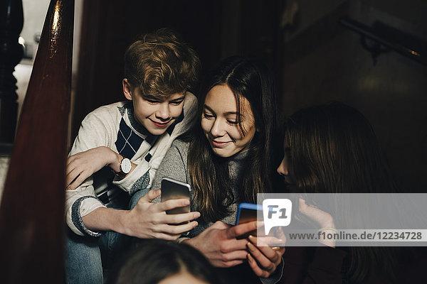Lächelnder Teenager  der weiblichen Freunden das Handy zeigt  während er auf einer Treppe sitzt.
