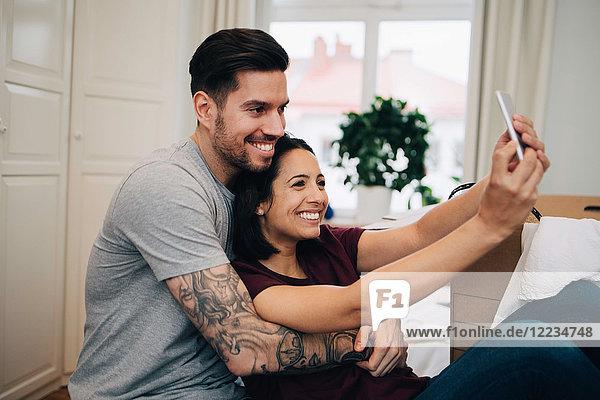 Glückliches Paar nimmt Selfie auf dem Handy  während es sich im Schlafzimmer ausruht.
