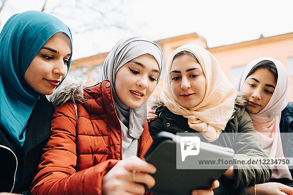 Low angle view of multi-ethnic Muslim friends sharing digital tablet
