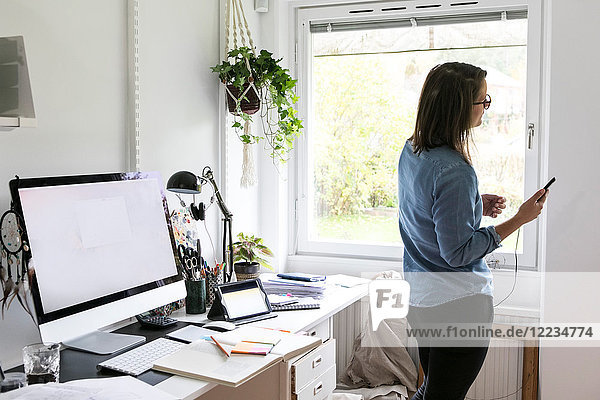 Side view of businesswoman using mobile phone while standing at home