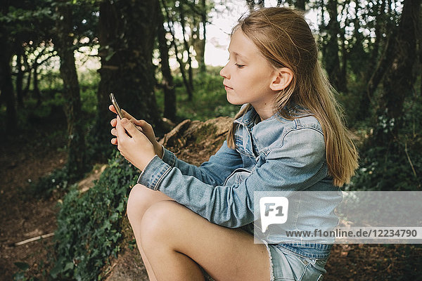 Side view of blond girl using smart phone in forest