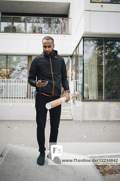 Nachdenklicher männlicher Arbeiter mit Paket mit Smartphone  während er gegen das Gebäude in der Stadt steht.