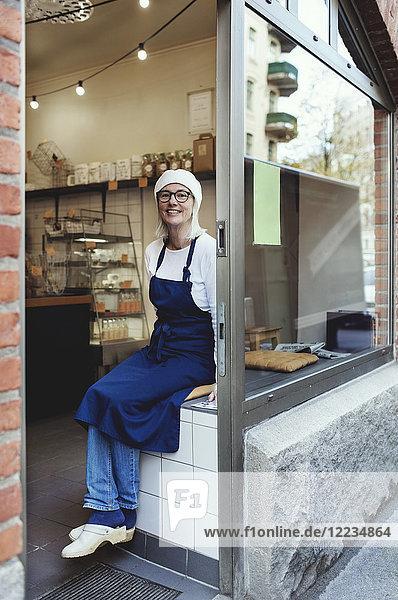 Porträt eines lächelnden Senior-Bäckers an der Kasse in der Bäckerei