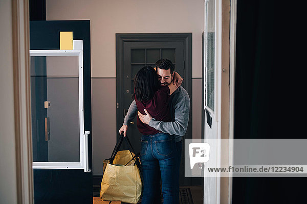 Woman embracing man with bag while standing in corridor seen from doorway