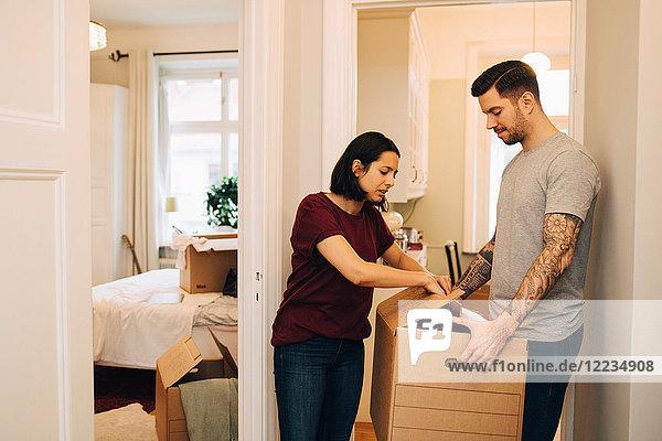 Frau packt Kiste aus  die vom Mann im Flur des neuen Hauses gehalten wird.