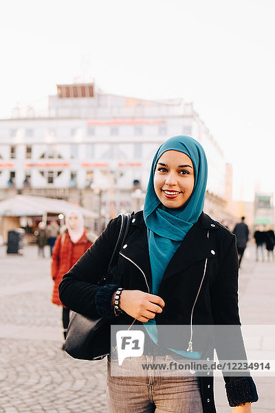 Portrait of smiling young Muslim woman wearing hijab walking on footpath in city