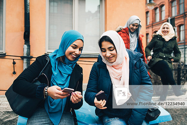 Smiling female friends sharing smart phones sitting against building in city
