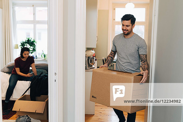Mann mit Box an der Tür  während Frau im Schlafzimmer telefoniert.