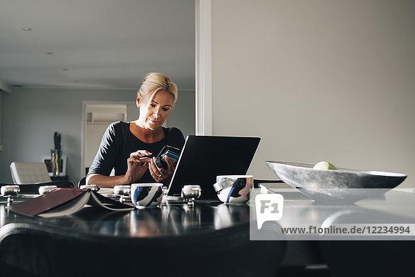 Reife blonde Frau mit Smartphone und Laptop auf dem Esstisch zu Hause