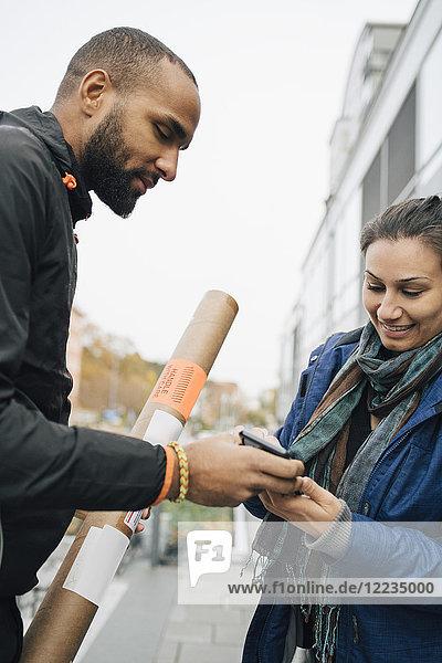 Lächelnde Frau unterschreibt am Handy für ihre Paketzustellung von männlichen Arbeitern