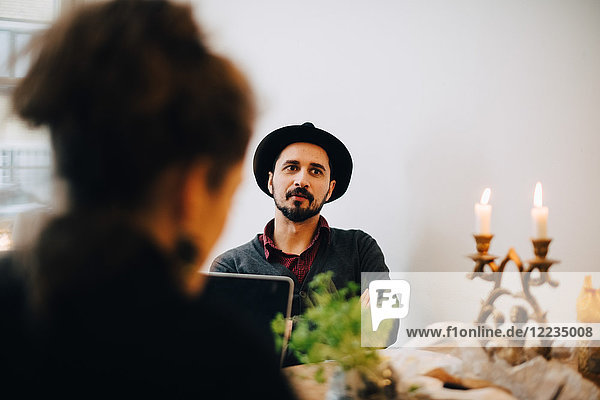 Geschäftsleute diskutieren am Tisch gegen die Wand im Kreativbüro