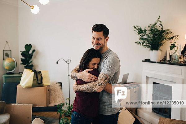 Lächelnder Mann  der die Frau umarmt  während er während des Umzugs im Wohnzimmer steht.