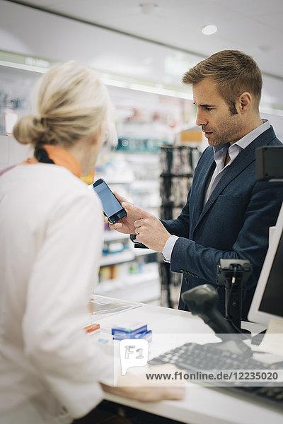 Reifer Mann zeigt Smartphone der Besitzerin an der Kasse in der Apotheke