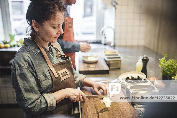 Reife Köchin beim Schneiden von Speisen an Bord an der Theke in der Restaurantküche