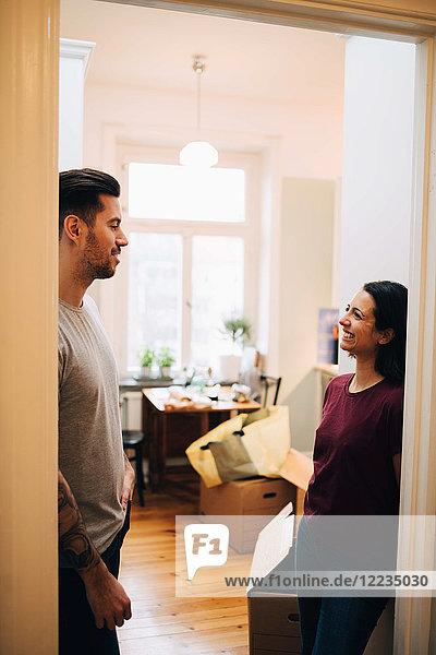 Lächelndes Paar  das vor der Tür im neuen Zuhause steht und redet