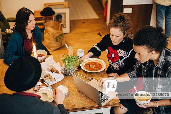 Blickwinkel auf Geschäftsleute  die über den Laptop diskutieren  während sie am Tisch im Kreativbüro zu Mittag essen.