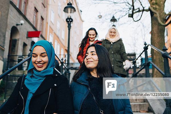 Niedriger Blickwinkel auf lächelnde multiethnische Freundinnen  die sich auf einer Treppe in der Stadt niederlassen.