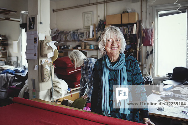 Porträt einer lächelnden Seniorin an der Werkbank in der Werkstatt