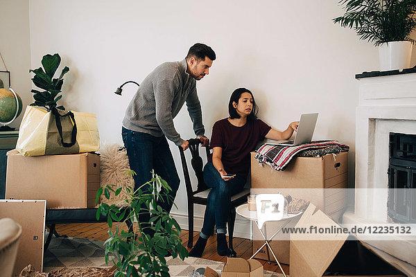 Frau zeigt Laptop dem Mann beim Umzug ins neue Zuhause