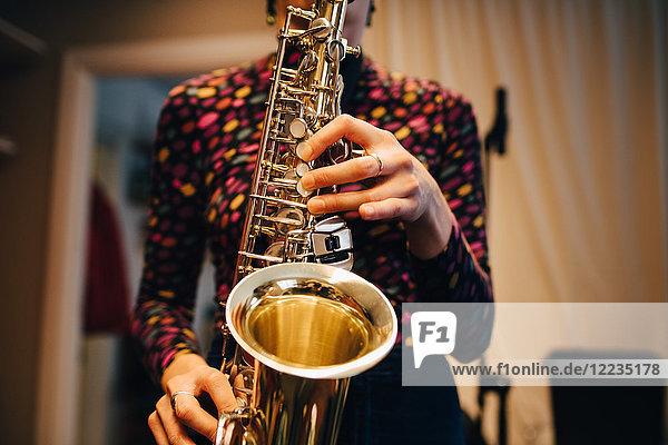 Mittelteil der Frau beim Saxophonspielen im Studio