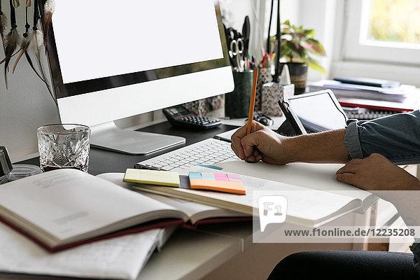 Abgeschnittene Hände der Geschäftsfrau beim Zeichnen auf dem Buch zu Hause