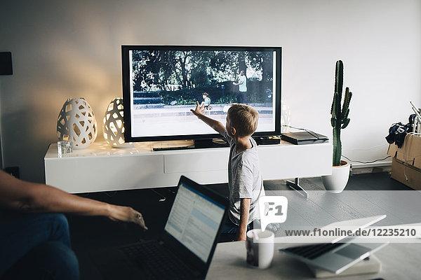 Volle Länge des Jungen kniend beim Berühren von Smart TV im Wohnzimmer zu Hause