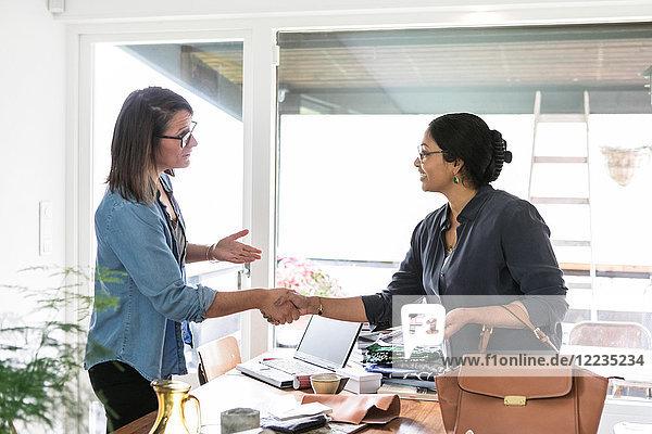 Mitarbeiterinnen beim Händeschütteln am Tisch im Home-Office