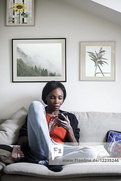 Volle Länge der mittleren erwachsenen Frau mit Handy auf dem Sofa zu Hause