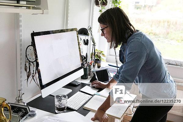 Seitenansicht der Geschäftsfrau mit dem Computer im Stehen zu Hause
