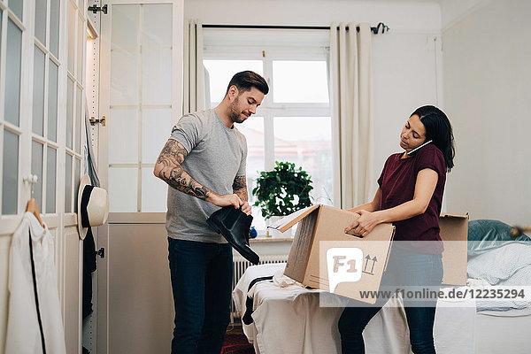 Mann  der Schuhe aus der Kiste zieht  während die Frau im neuen Zuhause telefoniert.