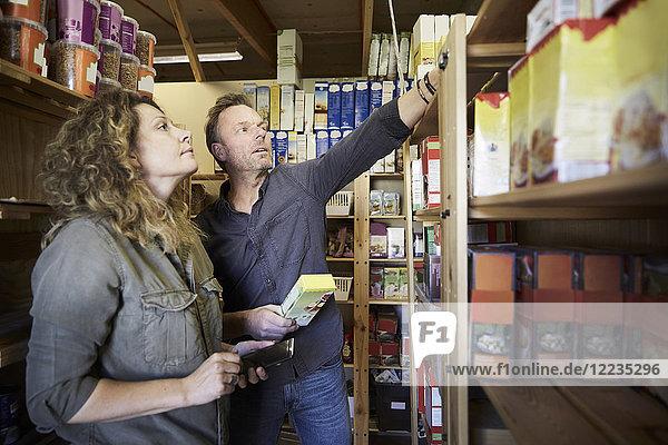 Reife Freiwillige bei der Untersuchung von Lebensmitteln im Lagerhaus
