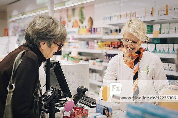 Lächelnde Besitzerin mit Senior-Kundin an der Kasse im Apothekenladen