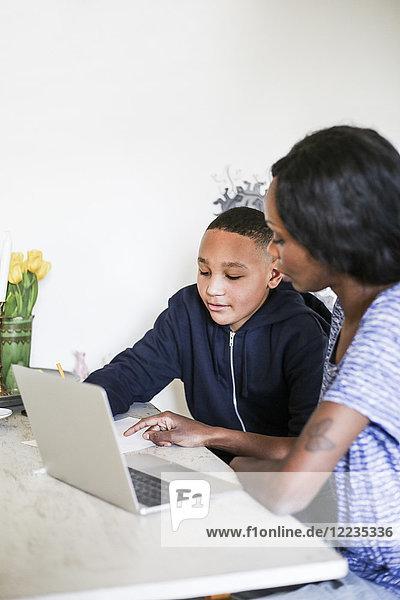 Mutter hilft Sohn bei den Hausaufgaben mit Laptop auf dem Tisch zu Hause