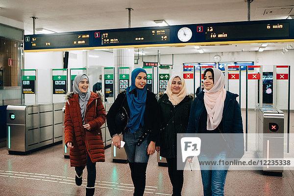Happy multi-ethnic Muslim friends walking at subway station