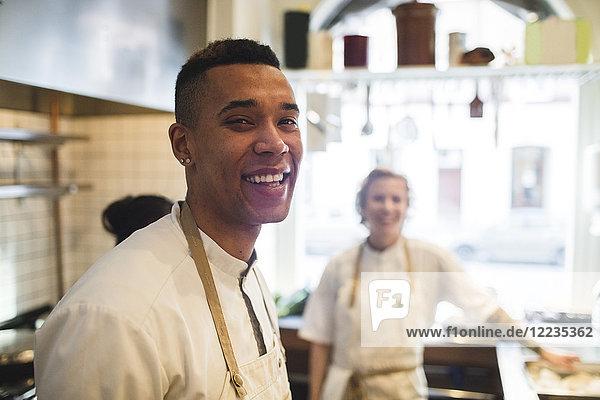 Porträt eines lächelnden jungen Kochs in der Restaurantküche mit Kollegen