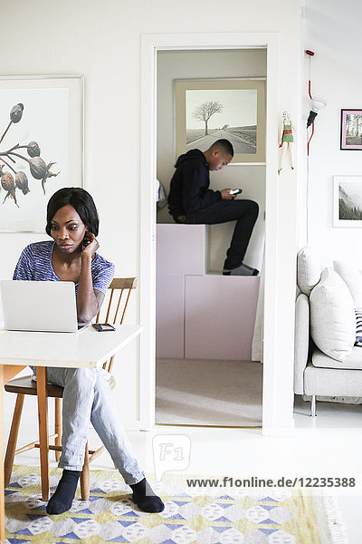 Mid adult woman using laptop at table with son sitting in storage room