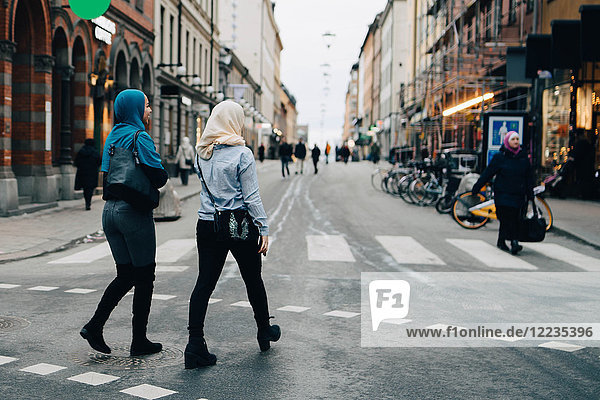 Full length rear view of young Muslim women walking on street in city