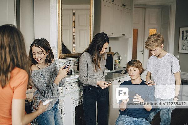 Männliche und weibliche Freunde beim Telefonieren im Wohnzimmer