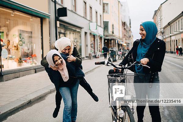 Junge Frau  die mit dem Fahrrad unterwegs ist und ein fröhliches Teenagermädchen sieht  das einem Freund auf der Straße in der Stadt Huckepack gibt.