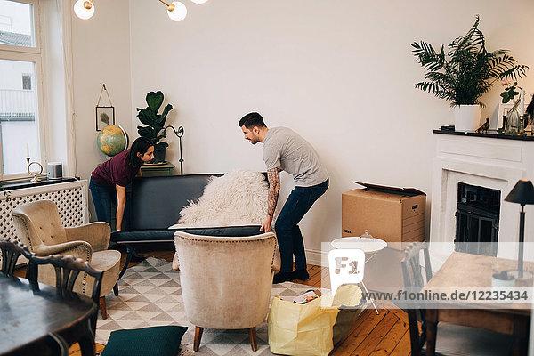 Mann und Frau arrangieren Sofa im Wohnzimmer