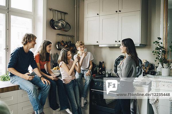Freunde fotografieren Mädchen durch Smartphone in der Küche