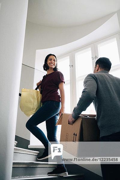 Lächelnde Frau  die mit einem Mann auf einer Treppe durchs Fenster geht.