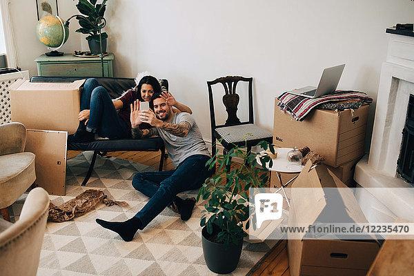 Lächelndes Paar Videoanrufe über Handy während des Umzugs im Wohnzimmer
