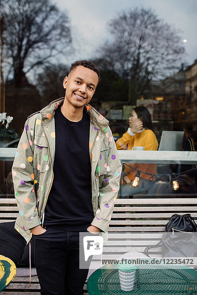 Portrait of smiling fashionable man standing with hands in pockets against cafe window