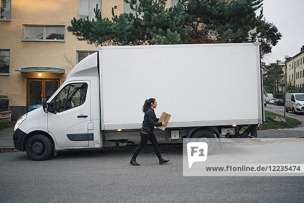 Arbeiterin  die eine Kiste trägt  während sie mit dem Lieferwagen auf der Straße in der Stadt unterwegs ist.